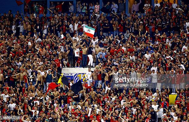 Atlas fans shout slogans in support of their team against Chivas during their Mexican Clausura 2015 tournament football match at Jalisco stadium in...