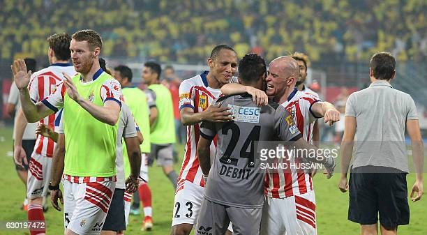 Atletico de Kolkata forward Iain Edward Hume hugs goalkeeper Debjit Majumder as they celebrate winning the Indian Super League final football match...