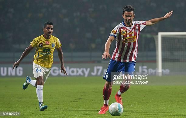 Atletico de Kolkata forward Marques Postiga kicks the ball as Kerala Blaster FC midfielder Mehtab Hossain looks on during the Indian Super League...