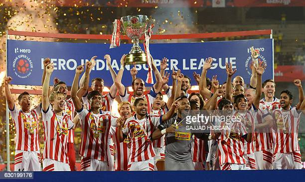 Atletico de Kolkata players celebrate with the trophy after winning the Indian Super League final football match against Kerala Blasters FC at the...