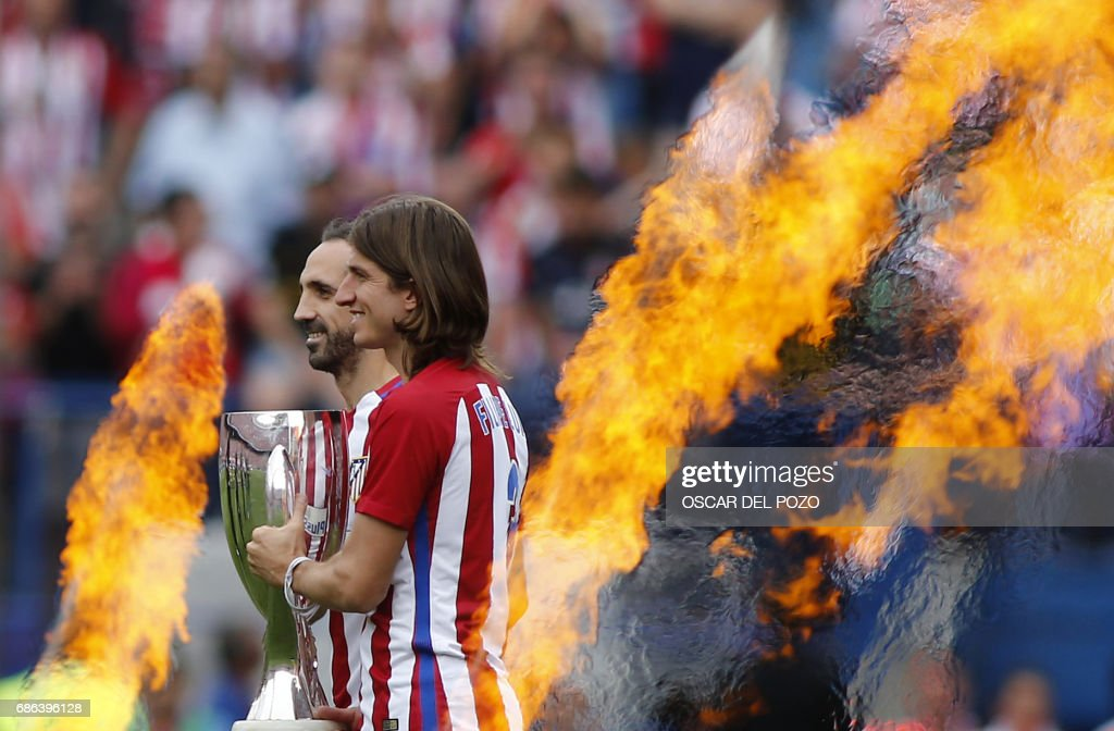 TOPSHOT - Atletico de Madrid's defender Juan Fran (L) and Felipe Luis carry a trophy as the walk between flames during a celebration bidding farewell to the team's stadium after the Spanish league football match Club Atletico de Madrid vs Athletic Club Bilbao at the Vicente Calderon stadium in Madrid on May 21, 2017. Atletico Madrid waved goodbye to their Vicente Calderon stadium by beating Athletic Bilbao 3-1 on Sunday. POZO