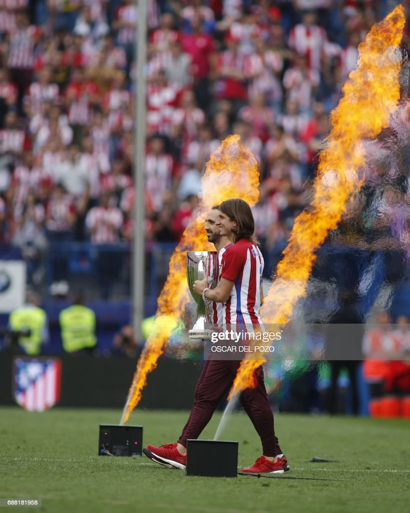 Atletico de Madrid's defender Juan Fran (L) and Felipe Luis carry a trophy as the walk between flames during a celebration bidding farewell to the team's stadium after the Spanish league football match Club Atletico de Madrid vs Athletic Club Bilbao at the Vicente Calderon stadium in Madrid on May 21, 2017. Atletico Madrid's mythical Vicente Calderon stadium will soon be history: sad news for supporters of Real Madrid's rivals but not so for locals who hope the neighbourhood will improve once noisy fans are gone. This weekend spells the end for the ageing structure that for over 50 years has housed Atletico Madrid -- not as well known abroad as the world-famous Real Madrid despite fielding players like French star Antoine Griezmann but with a huge following in the Spanish capital. POZO