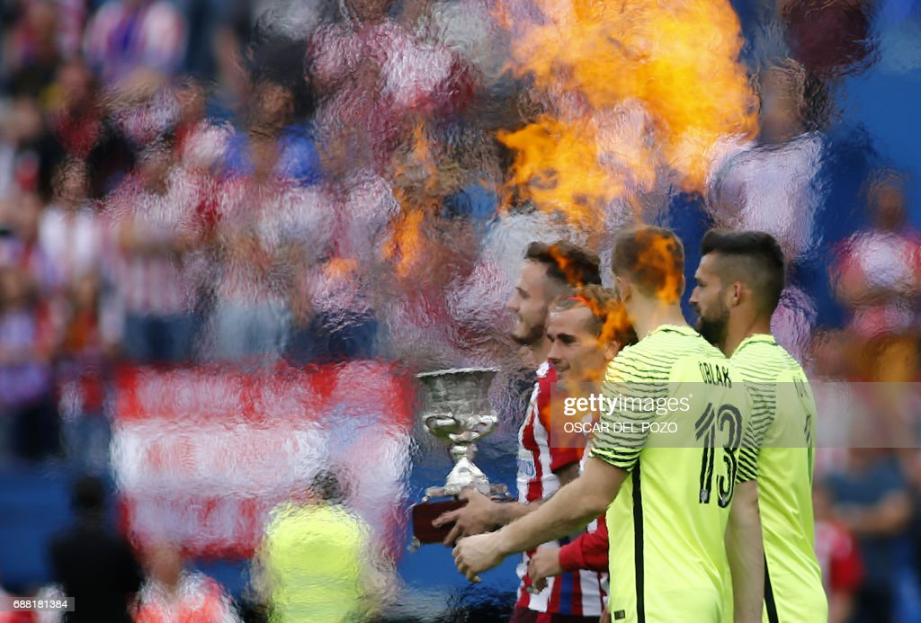 Atletico de Madrid's French forward Griezmann (C) carries a trophy as he walks between flames during a celebration bidding farewell to the team's stadium after the Spanish league football match Club Atletico de Madrid vs Athletic Club Bilbao at the Vicente Calderon stadium in Madrid on May 21, 2017. Atletico Madrid's mythical Vicente Calderon stadium will soon be history: sad news for supporters of Real Madrid's rivals but not so for locals who hope the neighbourhood will improve once noisy fans are gone. This weekend spells the end for the ageing structure that for over 50 years has housed Atletico Madrid -- not as well known abroad as the world-famous Real Madrid despite fielding players like French star Antoine Griezmann but with a huge following in the Spanish capital. VILLALOBOS