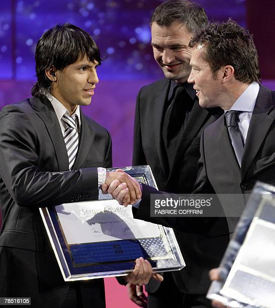 Atletico de Madrid's Sergio 'Kun' Aguero receives congratulation from former Swiss football player Stephane Chapuisat and legendary German former...