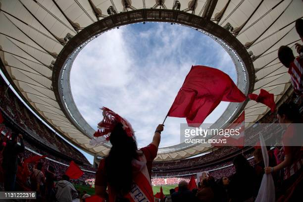 Atletico fans cheer up before the Spanish league women's football match between Club Atletico de Madrid and FC Barcelona at the Wanda Metropolitano...