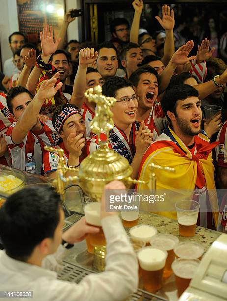 Atletico Madrid fans watch their team play Athletic Bilbao in the UEFA Europa League Final at a Madrid bar on May 9 2012 in Madrid Spain