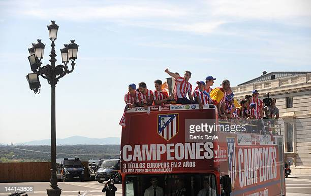 Atletico Madrid players arrive at the Almudena Cathedral on an open bus during celebrations a day after winning the Europa League Final on May 10...