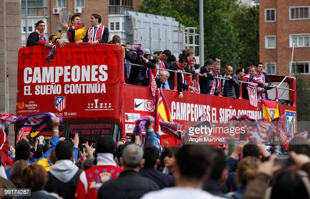 Atletico Madrid players celebrate on the top of an open bus in Madrid the day after Atletico won the UEFA Europa League Cup final on May 13 2010 in...