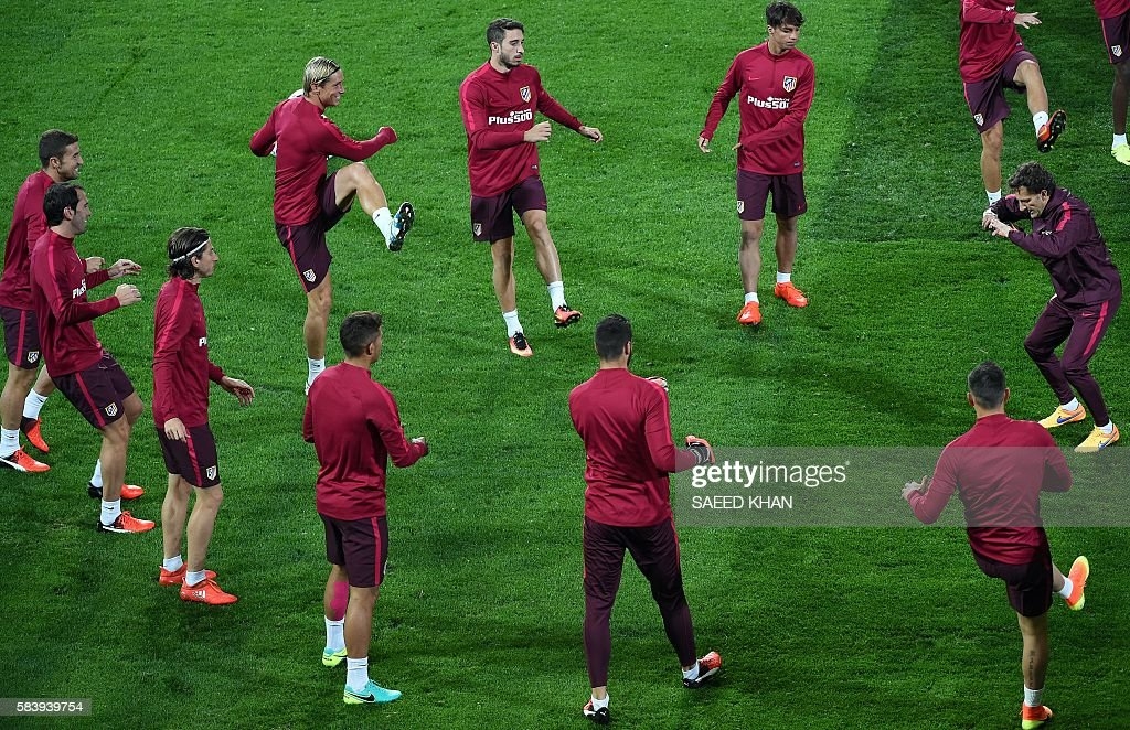 Atletico Madrid players engage in warmup exercises during a football training session at AAMI Park in Melbourne on July 28, 2016. / AFP / SAEED