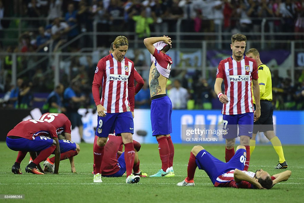 Atletico Madrid players look dejected after they lost the UEFA Champions League final football match to Real Madrid at San Siro Stadium in Milan, on May 28, 2016. / AFP / OLIVIER