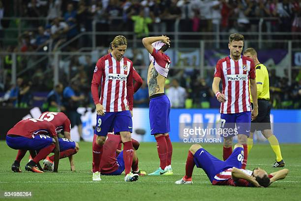 Atletico Madrid players look dejected after they lost the UEFA Champions League final football match to Real Madrid at San Siro Stadium in Milan on...