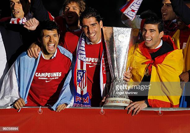 Atletico Madrid players Sergio Aguero Raul Garcia and Jose Antonio Reyes celebrate with the trophy at the Neptuno fountain in Madrid the day after...