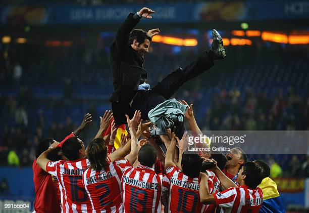Atletico Madrid players throw their head coach Quique Sanchez Flores in the air celebrating winning the UEFA Europa League trophy after extra time...