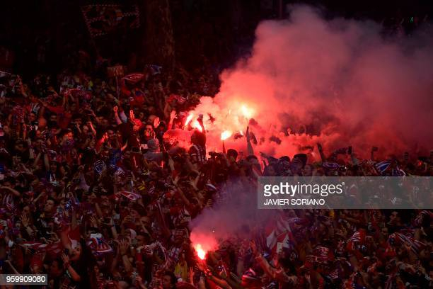 Atletico Madrid supporters light flares as they wait for the players to arrive aboard an opentop bus during a parade celebrating their Europa League...