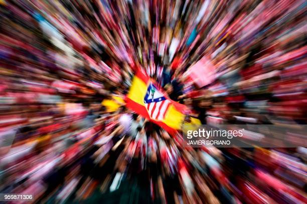 Atletico Madrid supporters wave the club's flag as they wait for the players to arrive aboard an opentop bus during a parade celebrating their Europa...