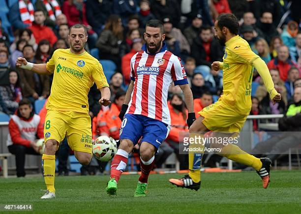 Atletico Madrid's Arda Turan vies with Getafe's Medhi Lacen during the Spanish La Liga football match between Atletico Madrid and Getafe CF at the...