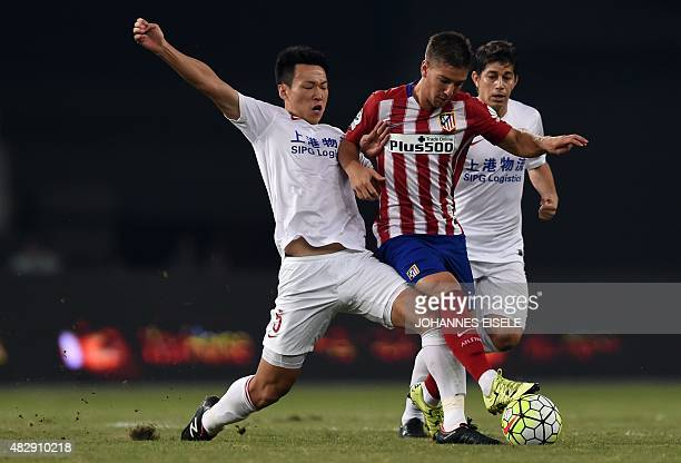 Atletico Madrid's Argentina forward Luciano Vietto is challenged by Shanghai's midfielder Jiajie Wang and Argentinian forward Dario Conca during a...