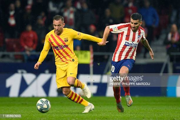 Atletico Madrid's Argentine forward Angel Correa challenges Barcelona's Brazilian midfielder Arthur during the Spanish league football match between...