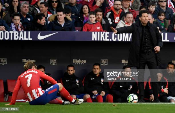 Atletico Madrid's Argentinian coach Diego Simeone gestures as Atletico Madrid's French forward Antoine Griezmann sits on the field during the Spanish...