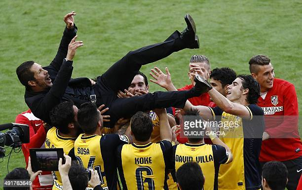 Atletico Madrid's Argentinian coach Diego Simeone is tossed by teammates as they celebrate their Spanish league title at the end of the Spanish...