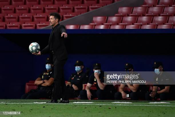 Atletico Madrid's Argentinian coach Diego Simeone prepares to pass the ball back to players during the Spanish League football match between Atletico...