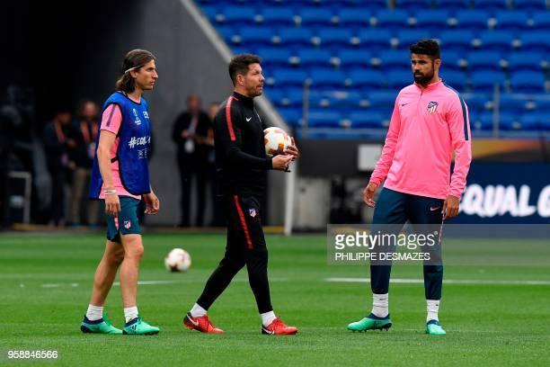 Atletico Madrid's Argentinian coach Diego Simeone walks between Atletico Madrid's Brazilian defender Filipe Luis and Atletico Madrid's Spanish...