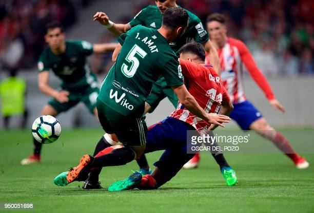 Atletico Madrid's Argentinian forward Angel Correa vies with Real Betis' Spanish defender Jordi Amat during the Spanish league football match between...