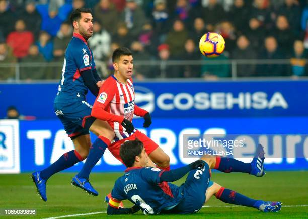 Atletico Madrid's Argentinian forward Angel Correa vies with SD Huesca's Spanish defender Pablo Insua and SD Huesca's Spanish defender Xabier Etxeita...