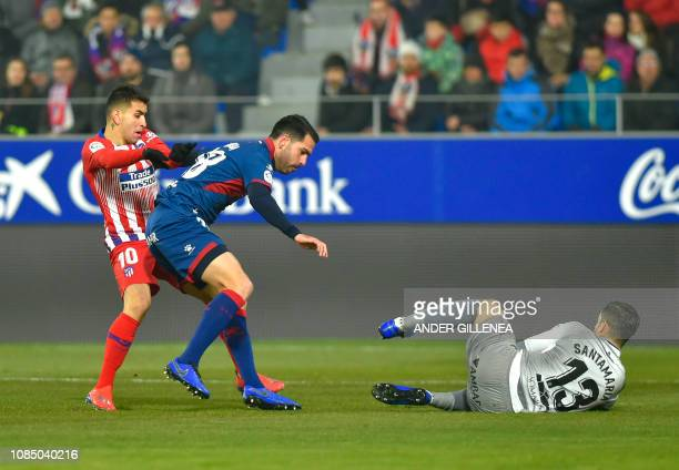 Atletico Madrid's Argentinian forward Angel Correa vies with SD Huesca's Spanish defender Pablo Insua in front of SD Huesca's Spanish goalkeeper...