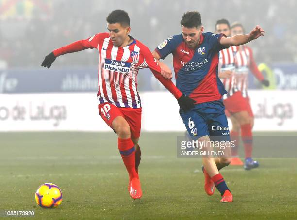 Atletico Madrid's Argentinian forward Angel Correa viies for the ball with SD Huesca's Spanish midfielder Moi Gomez during the Spanish League...