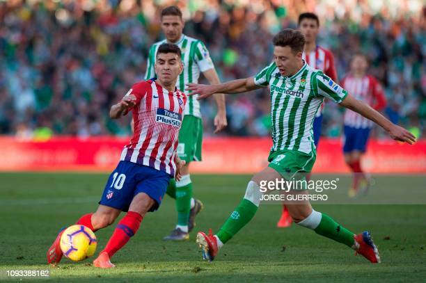 Atletico Madrid's Argentinian forward Angel Martin Correa fights for the ball with Real Betis' Spanish defender Francisco Guerrero during the Spanish...