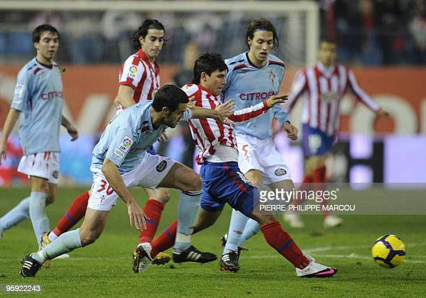 Atletico Madrid's Argentinian forward Sergio Aguero vies with Celta de Vigo's Spanish midfielder Jonathan Vila and Spanish midfielder Miguel Pérez...