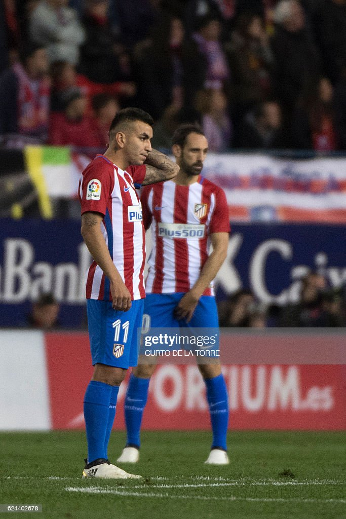 Atletico Madrid's Argentinian midfielder Angel Correa (L) and Atletico Madrid's Uruguayan defender Diego Godin wait to kick off following a goal of Real Madrid during the Spanish league football match Club Atletico de Madrid vs Real Madrid CF at the Vicente Calderon stadium in Madrid, on November 19, 2016. / AFP / CURTO