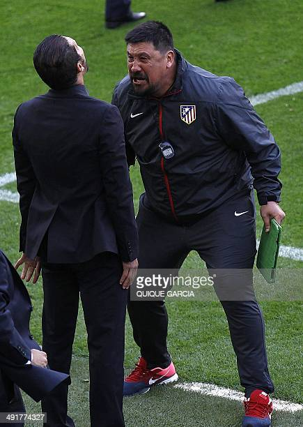 Atletico Madrid's assistant coach German El Mono Burgos celebrates with Atletico de Madrid's Argentinian coach Diego Simeone at the end of the...