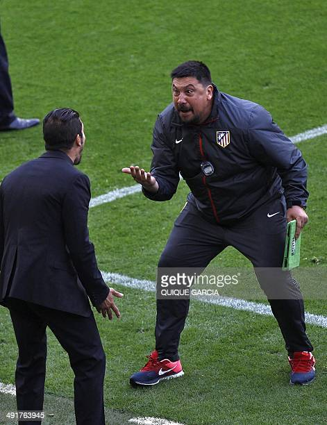 Atletico Madrid's assistant coach German El Mono Burgos reacts past Atletico de Madrid's Argentinian coach Diego Simeone during the Spanish league...