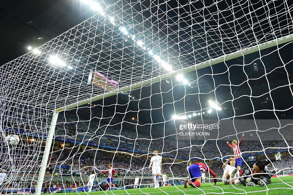 TOPSHOT - Atletico Madrid's Belgian forward Yannick Ferreira Carrasco (C) reacts after scoring a goal past Real Madrid's Costa Rican goalkeeper Keylor Navas (R) during the UEFA Champions League final football match between Real Madrid and Atletico Madrid at San Siro Stadium in Milan, on May 28, 2016. / AFP / OLIVIER