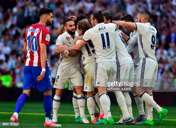 Atletico Madrid's Belgian forward Yannick Ferreira Carrasco walks past Real Madrid players celebrating their opening goal during the Spanish league...