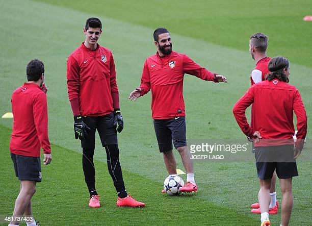 Atletico Madrid's Belgian goalkeeper Thibaut Courtois and Atletico Madrid's Turkish midfielder Arda Turan take part in a training session at the Camp...