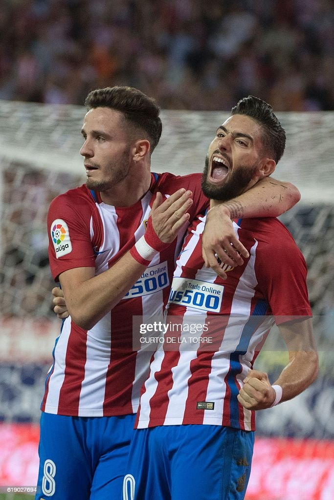 Atletico Madrid's Belgian midfielder Yannick Ferreira Carrasco (R)celebrates after scoring with teammate Atletico Madrid's midfielder Saul Niguez during the Spanish league football match between Club Atletico de Madrid and Malaga CF at the Vicente Calderon stadium in Madrid on October 29, 2016. / AFP / CURTO