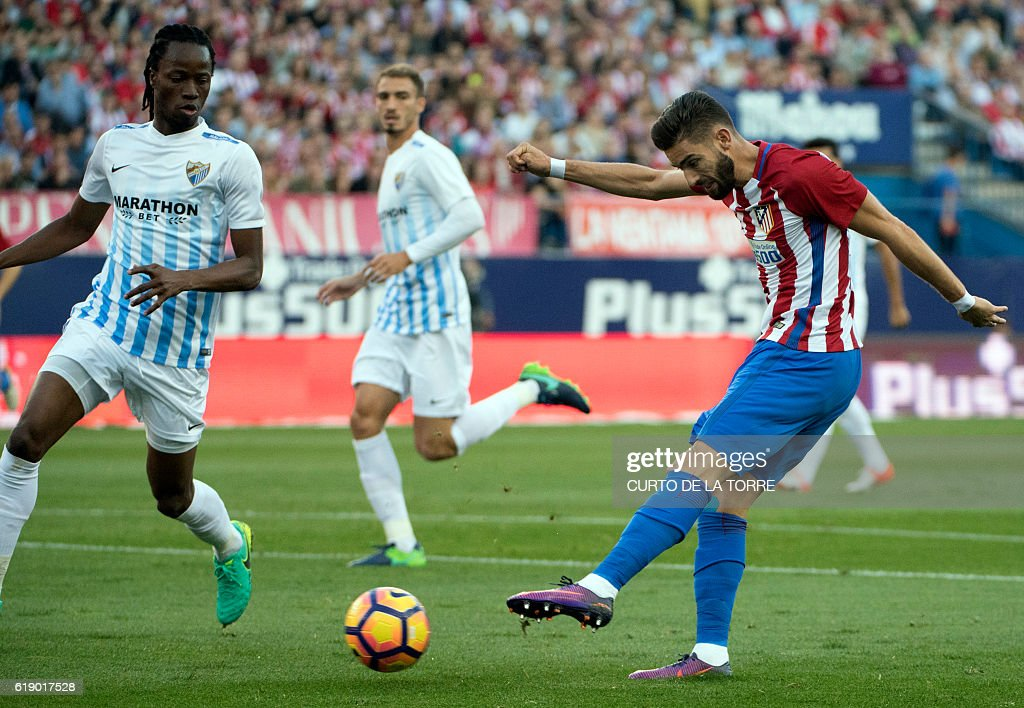 Atletico Madrid's Belgian midfielder Yannick Ferreira Carrasco (R) shoots to score a goal during the Spanish league football match between Club Atletico de Madrid and Malaga CF at the Vicente Calderon stadium in Madrid on October 29, 2016. / AFP / CURTO