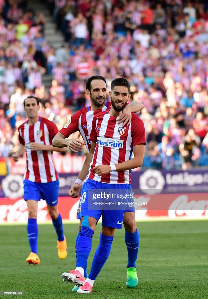 Atletico Madrid's Belgian midfielder Yannick Ferreira Carrasco (R) celebrates with Atletico Madrid's defender Juanfran after scoring during the Spanish league football match Atletico de Madrid vs Osasuna at the Vicente Calderon stadium in Madrid on April 15, 2017. /