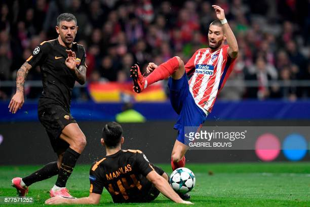 Atletico Madrid's Belgian midfielder Yannick FerreiraCarrasco challenges Roma's Croatian defender Aleksandar Kolarov and Roma's Greek defender Kostas...
