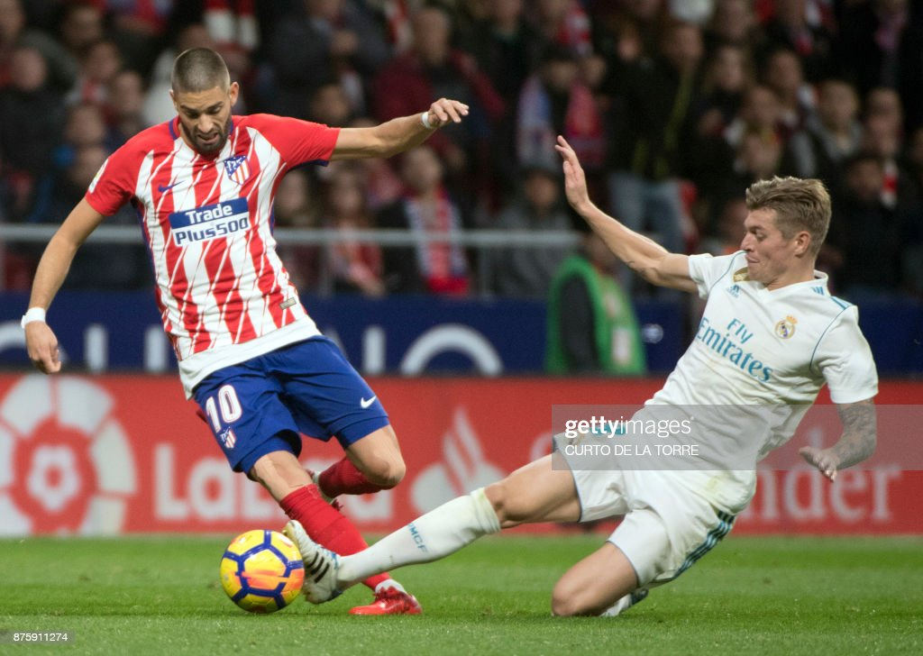 TOPSHOT - Atletico Madrid's Belgian midfielder Yannick Ferreira-Carrasco (L) vies with Real Madrid's German midfielder Toni Kroos during the Spanish league football match Atletico Madrid vs Real Madrid at the Wanda Metropolitan stadium in Madrid on November 18, 2017. /