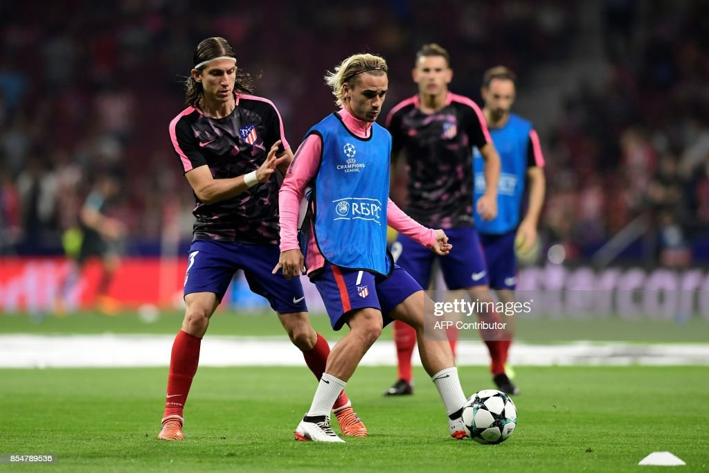 Atletico Madrid's Brazilian defender Filipe Luis (L) vies with Atletico Madrid's French forward Antoine Griezmann as they warm up before the UEFA Champions League Group C football match Club Atletico de Madrid vs Chelsea FC at the Metropolitan stadium in Madrid on September 27, 2017. /