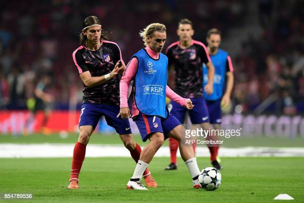 Atletico Madrid's Brazilian defender Filipe Luis vies with Atletico Madrid's French forward Antoine Griezmann as they warm up before the UEFA...