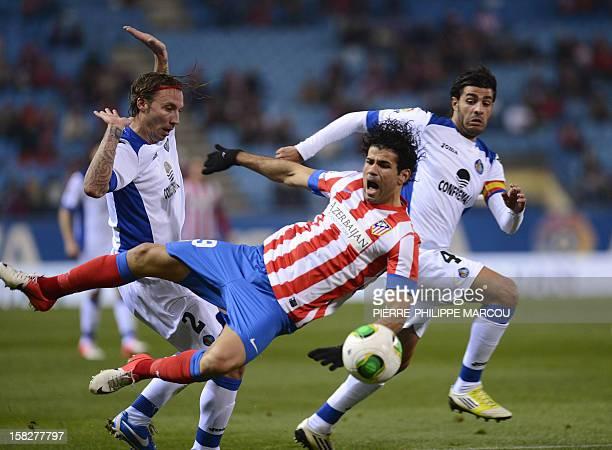 Atletico Madrid's Brazilian forward Diego da Silva Costa vies with Getafe's defender Alexis Ruano Delgado and Getafe's defender Miguel Torres during...
