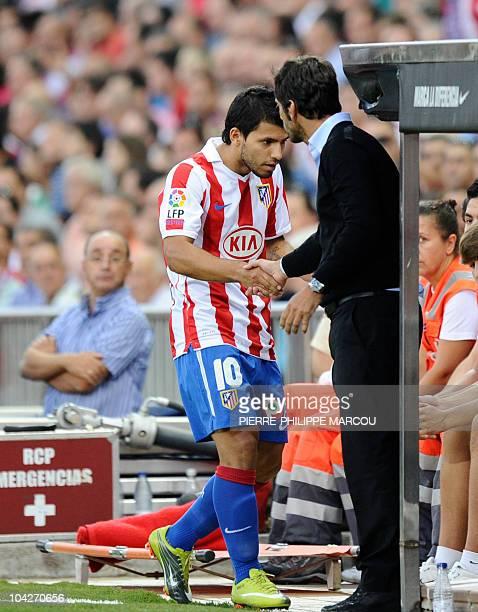Atletico Madrid's coach Quique Sanchez Flores shakes hands with Atletico Madrid's Argentinian forward Sergio Kun Aguero during a Spanish League...