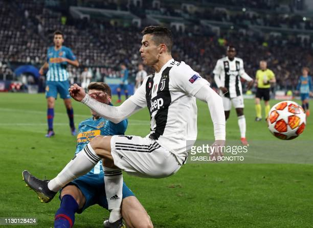 Atletico Madrid's Colombian defender Santiago Arias tackles Juventus' Portuguese forward Cristiano Ronaldo during the UEFA Champions League round of...