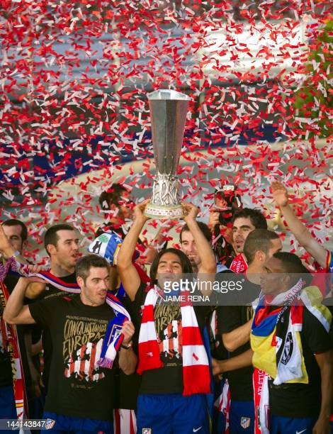 Atletico Madrid's Colombian Radamel Falcao Atletico Madrid's captain Antonio Lopez and Colombian Luis Perea celebrate with supporters at the Neptuno...