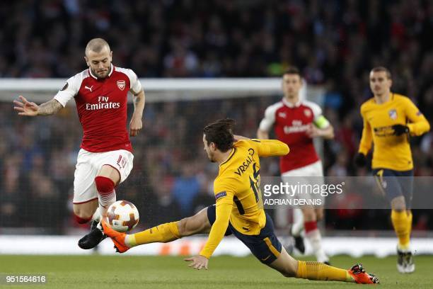 Atletico Madrid's Croatian defender Sime Vrsaljko receives his first yellow card for this challenge on Arsenal's English midfielder Jack Wilshere...